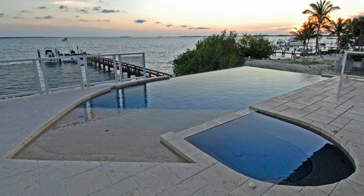 Pebble Finish With A Shallow Lounging Area, Pool Spa Combo And Infinity Edge
